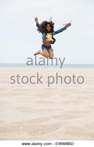Ritratto ragazza esuberante salto sulla spiaggia Foto Stock