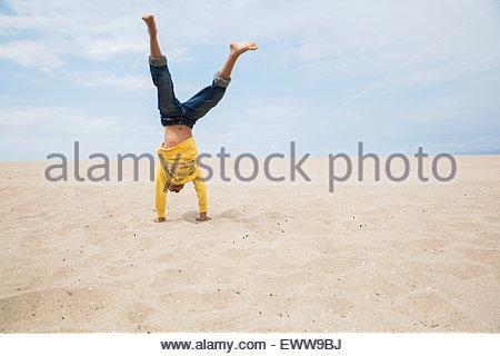 Ragazzo facendo handstand sulla spiaggia Foto Stock