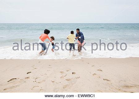 Famiglia giocando in oceano in spiaggia Foto Stock