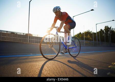 Ciclista maschio ciclismo su pista al velodromo, all'aperto Foto Stock