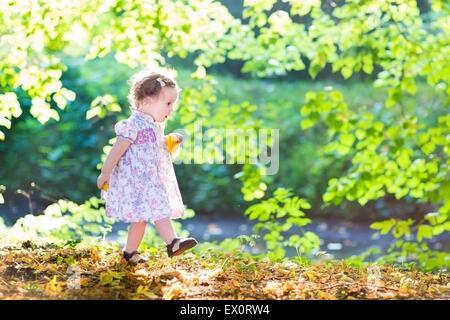 Bellissimo bambino ragazza in un abito rosa camminare al fianco di un fiume in un posto molto soleggiato giorno Foto Stock