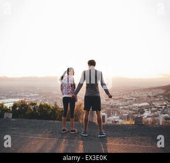 Vista posteriore di una giovane coppia in piedi insieme a sunrise. Per chi ama fare jogging sulla collina nella Foto Stock
