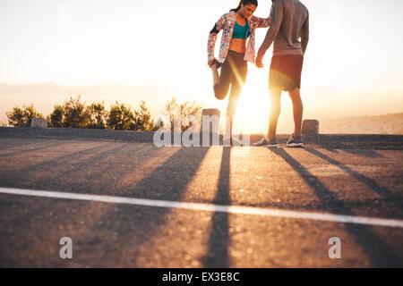 Colpo all'aperto di giovani praticanti di jogging stretching prima di una corsa la mattina. Giovane uomo e donna Foto Stock
