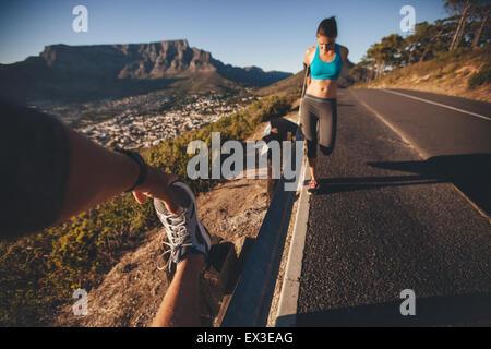 POV shot dell uomo che allunga la gamba con la donna che esercitano da una barriera di sicurezza stradale. Giovani Foto Stock