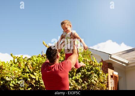Giovane uomo il sollevamento di sua figlia in aria in alto. Felice padre e figlia a giocare nel loro cortile in Foto Stock