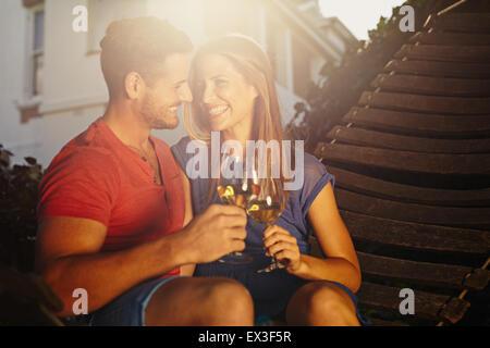Felice coppia giovane seduto su amaca vino di tostatura e guardando ogni altra sorridente. Amorevole coppia giovane rilassante con un bicchiere