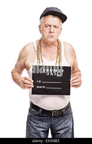 ... guardando la telecamera e appoggiata contro un arrugginito muro grigio   Colpo verticale di un gangster senior in un hip hop vestito in posa per una  ... 9504814b1672