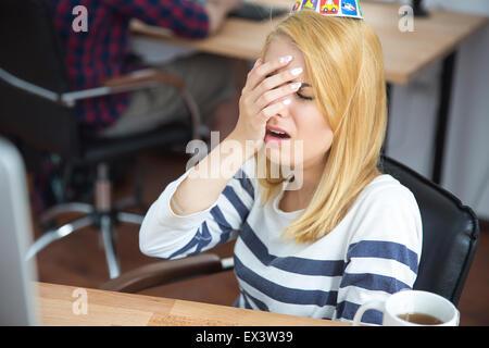 Frustrati giovane donna seduta al tavolo in ufficio Foto Stock