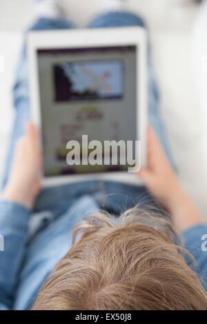 Vista posteriore del giovane ragazzo giocando sulla tavoletta digitale Foto Stock