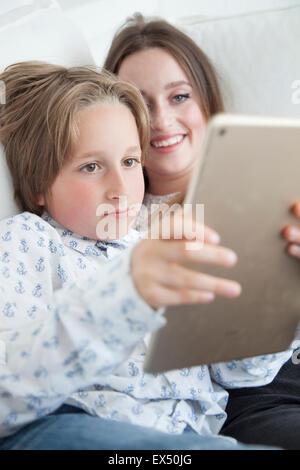 Ragazzo e ragazza adolescente utilizzando tavoletta digitale Foto Stock