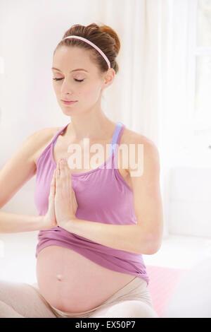 Donna incinta meditando con le mani insieme