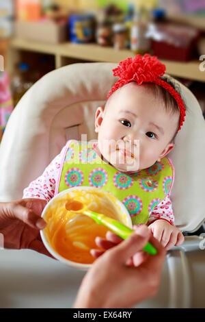 Baby mangiare cibo solido Foto Stock