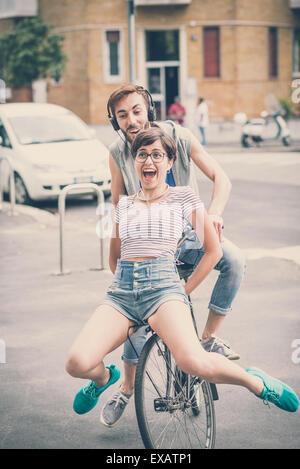 Coppia di amici giovane uomo e donna Bicicletta Equitazione nella città Foto Stock