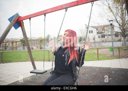 Giovane bella capelli rossi donna venezuelana lo stile di vita nella città di Milano per divertirsi al parco giochi Foto Stock
