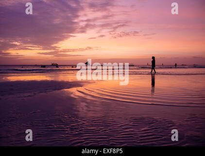 Stagliano giovane donna sulla spiaggia al tramonto, Boracay Island, Visayas, Filippine Foto Stock