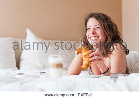 Giovane donna avente la colazione a letto Foto Stock