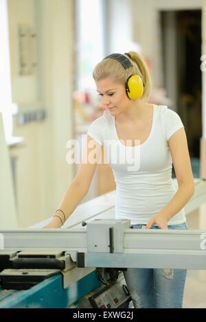 Giovane donna lavora in una falegnameria su un buzzsaw Foto Stock