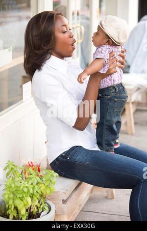 Ritratto di donna sorridente holding figlio (12-17 mesi) Foto Stock