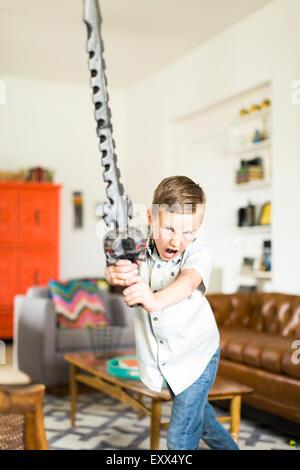 Ragazzo (6-7) giocando con la spada Foto Stock