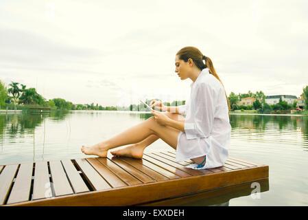 Donna relax sul lago di dock con tavoletta digitale Foto Stock