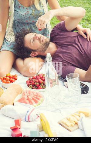 L'uomo godendo un picnic con accompagnatore Foto Stock