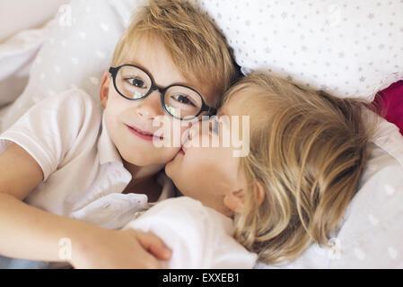 Piccola ragazza baciare il grande fratello Foto Stock