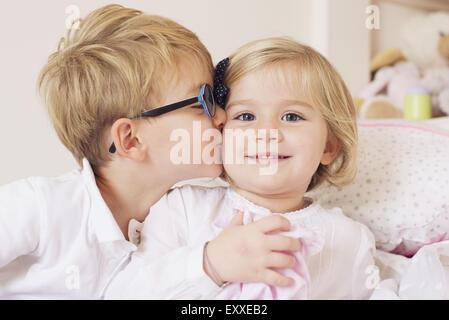 Ragazzo baciare la sorella sua guancia Foto Stock
