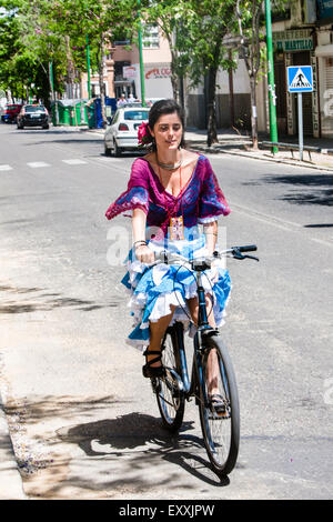 Giovane donna sulla bicicletta nel tradizionale abito di Siviglia a Siviglia, centro di Siviglia, in Andalusia, Foto Stock