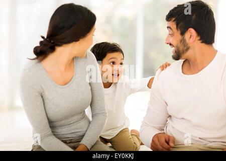 Felice giovani indiani giovane con il loro figlio seduto sul letto di casa Foto Stock