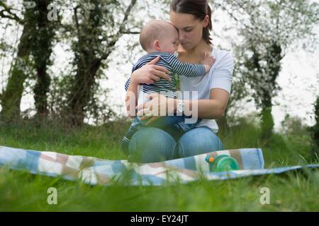 Giovane madre abbracciando baby figlio sulla coperta picnic nel campo Foto Stock