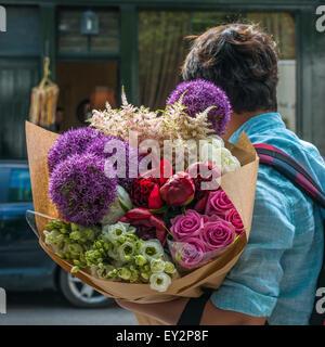 Una persona che porta un grande mucchio di coloratissimi fiori misti hanno acquistato presso la Columbia Road flower market di domenica mattina Foto Stock