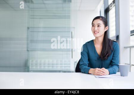 Giovane imprenditrice pensando in ufficio Foto Stock