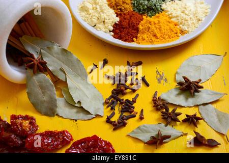 Cucina colorata le spezie e le erbe su un piatto rotondo con bastoncini di cannella, foglie di alloro e anice stellato Foto Stock