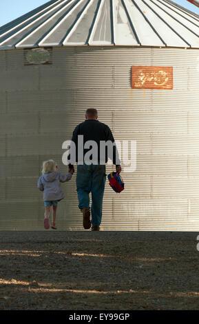 Figlia,agricoltore,tenendo le mani,Iowa,Silo Foto Stock