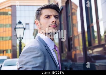 Ritratto di un imprenditore pensieroso in piedi all'aperto vicino edificio per uffici e guardando lontano Foto Stock