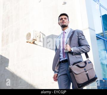 Ritratto di un imprenditore bello in piedi all'aperto vicino edificio per uffici Foto Stock