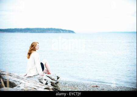Giovane donna seduta sulla spiaggia che guarda al mare, Bainbridge Island, nello Stato di Washington, USA Foto Stock