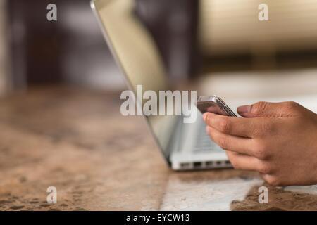 Mano del ragazzo adolescente al tavolo da pranzo texting sullo smartphone Foto Stock