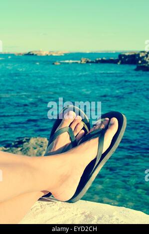 Primo piano dei piedi di un uomo con flip-flop che è rilassante vicino al mare in estate, filtrata Foto Stock