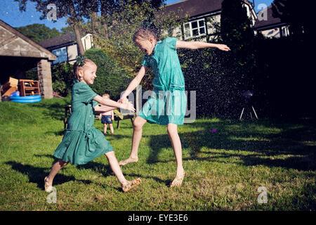 Due bambini nella scuola abiti estivi, in esecuzione attraverso un soffione di erogazione dell'acqua. Foto Stock