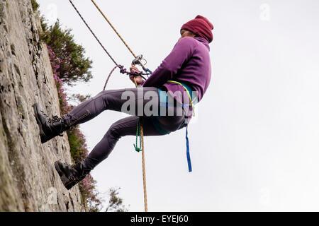 Female Rock scalatore la discesa in corda doppia giù con la fune di sicurezza e cablaggio di arrampicata su un rockface. Foto Stock