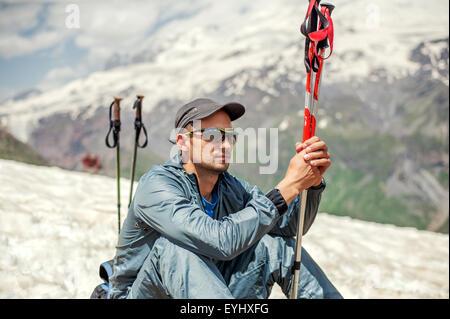 Giovane uomo alpinista seduto su un pendio di neve vicino alla sommità del monte Cheget e azienda trekking pole. Foto Stock