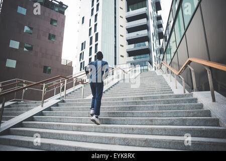 Vista posteriore del giovane maschio runner acceso fino città scale Foto Stock