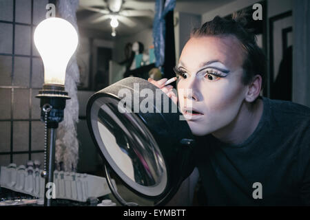 Maschio di drag queen mettendo su make up e vestirsi in prepration per una performance Foto Stock