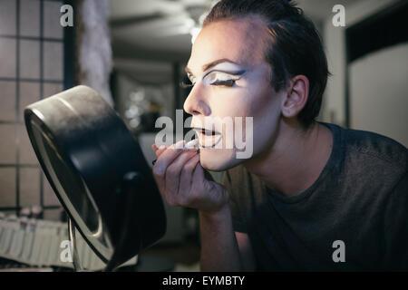 Maschio di drag queen mettendo su make up e vestirsi in preparazione per una performance