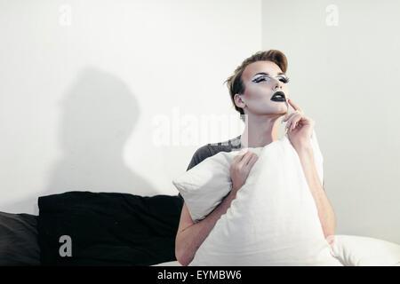 Maschio di drag queen in posa per pin-up stile ritratto glamour a casa.