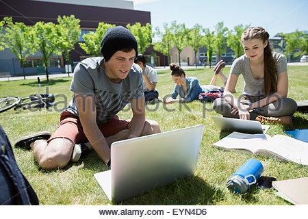 Gli studenti con i notebook Studio sul soleggiato prato del campus Foto Stock