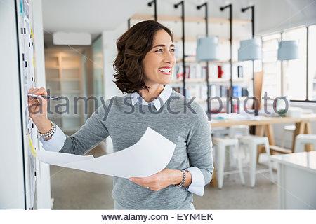 Architetto sorridente con blueprint a lavagna in office Foto Stock