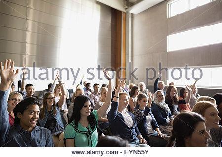 Gli studenti alzando le mani in auditorium pubblico Foto Stock