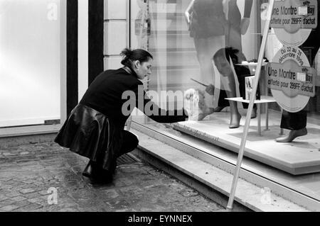 Giovane bella femmina la pulizia della finestra di un boutique Hotel in rouen Francia Foto Stock